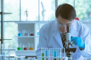HGH scientist adjusting the microscope for his experiments in laboratory room  300x200