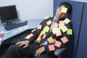 businessman asleep at desk with notes_HFCbCfCrs 300x200