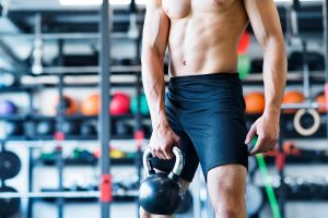 unrecognizable young fit man doing strength training exercising with kettlebell in mod SBI 305238209 300x200