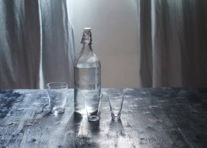 graphicstock glass of water with a bottle on wooden table_SdFxUYoDgog 300x214